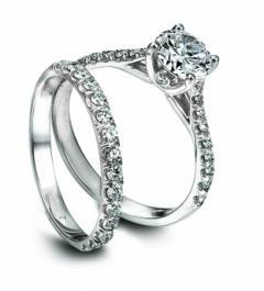 Platinum engagement ring and wedding band set with a solitaire diamond and channel set diamonds surr