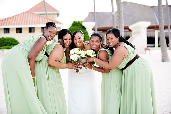 This bride is surrounded by her lovely bridesmaids in light green dresses with brown sashes.
