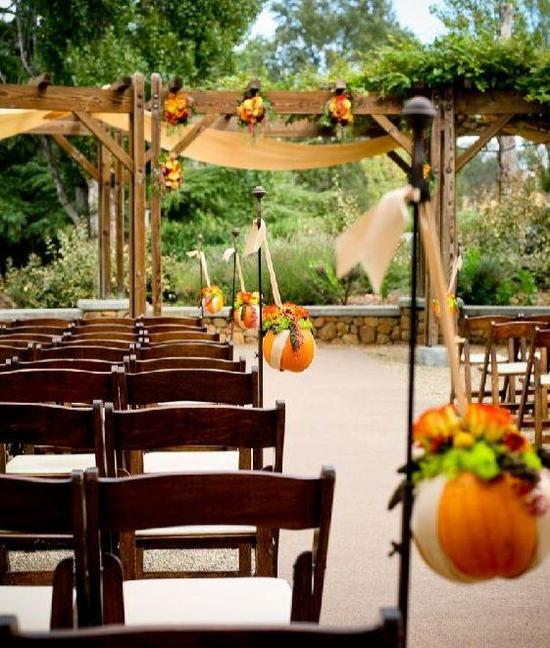 Beautiful outdoor wedding ceremony during fall, with pumpkin and floral wedding details & decor