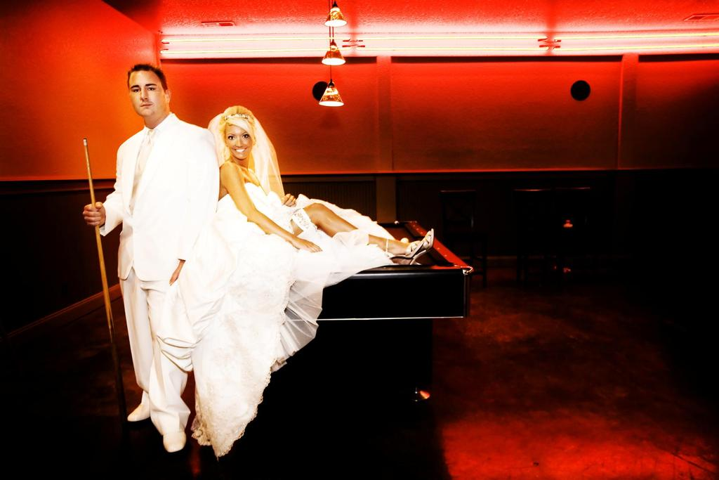 Bride in white strapless wedding dress, groom in white tux, sit on pool table in vibrant red room
