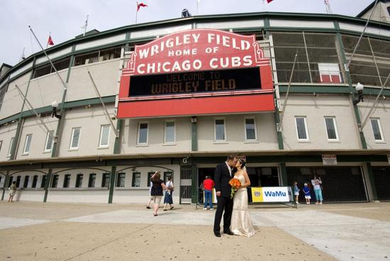 Bride and groom kiss in front of Chicago's Wrigley Field