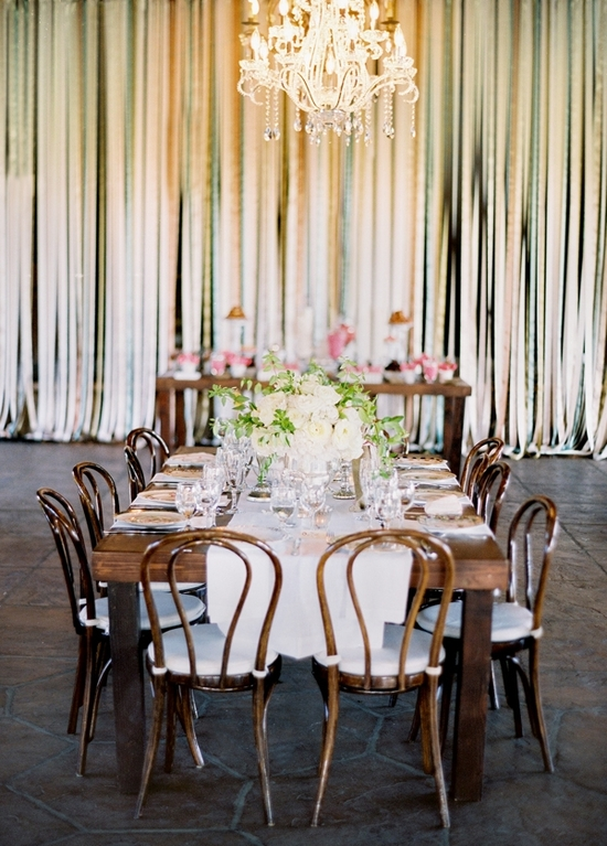Beautiful wedding ceremony decor, with ribbon wall, chandelier and pink flowers