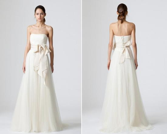 Simple and romantic ivory wedding dress from Vera Wang with light baby pink sash that ties at natura