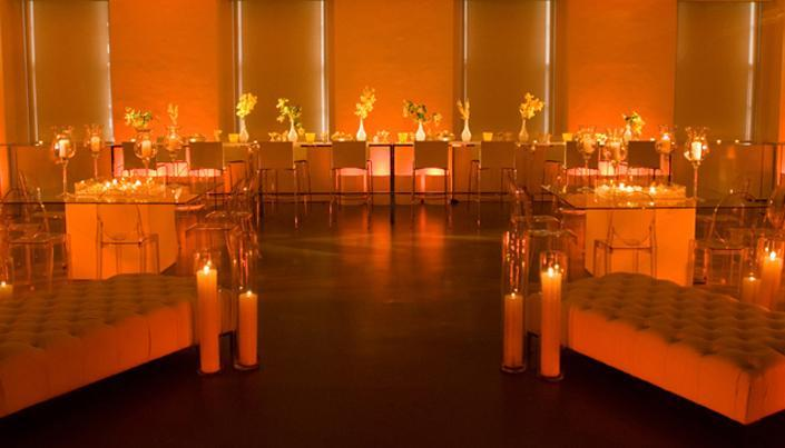 Beautiful orange, amber and yellow wedding reception room with clear tables and chairs