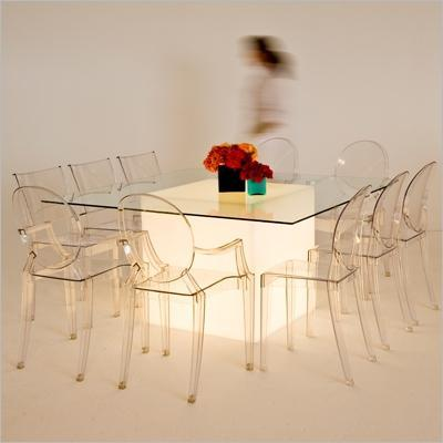 Sleek and clean tablescape with clear table and chairs, lighted box below and colorful flowers on to