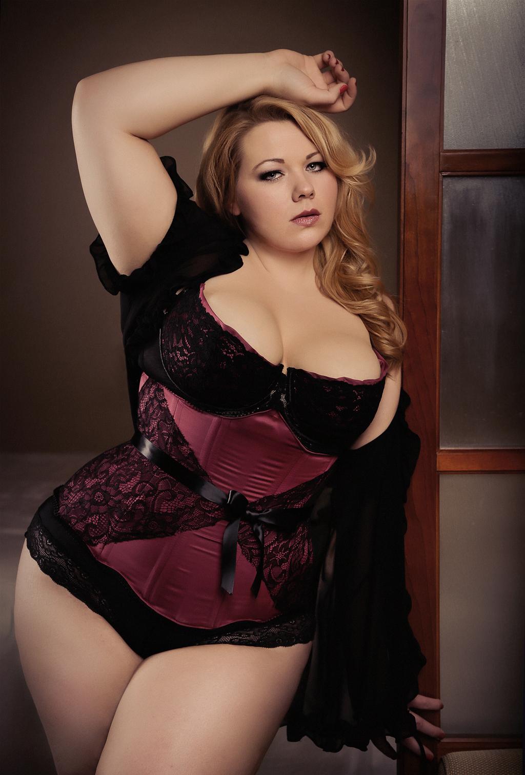Sexy plump woman sitting on pink background stock photo