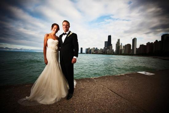 Beautiful bride and groom pose in front of Chicago's skyline and Lake Michigan