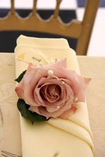 Perfect for a whimsical wedding vibe, an ivory folded napkin with light pink rose adorned with pearl