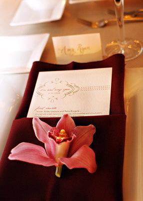 Tablescape at wedding reception with chocolate brown napkin and pink orchid