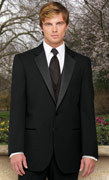 photo of This handsome blond groom wears a black two-button tuxedo with silk lapels and a black silk tie and