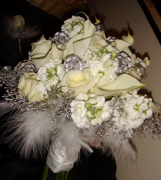This bouquet features ivory roses and green and silver accent colors