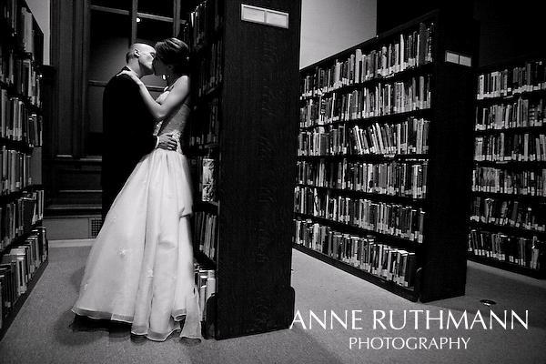 Black And White Wedding Photo Bride Groom Kiss Against Book Shelves At Library
