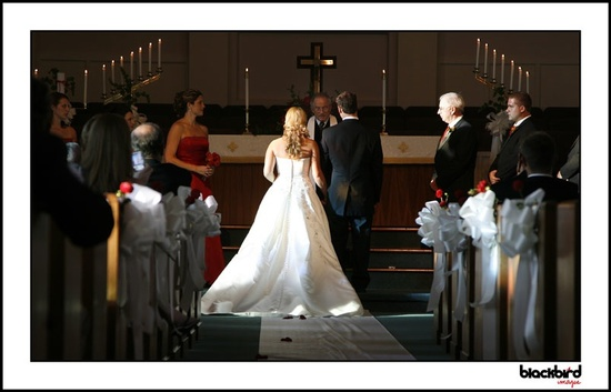This bride's full skirted, backless wedding dress looks elegantly traditional in the church setting.