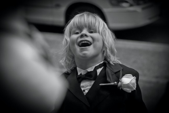 This child is clearly enjoying the wedding and looks perfect in his child's tuxedo with oversized fl
