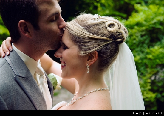 Groom kisses beautiful bride on her forehead as she smiles, forest in background