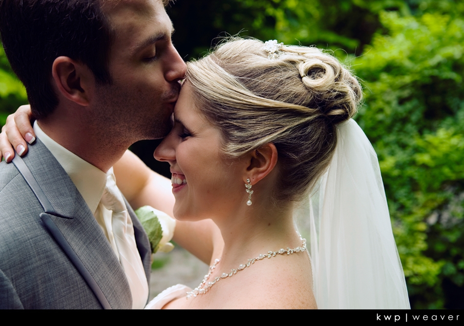 Kwp-groom-lovingly-kisses-brides-forehead-grey-tux-ivory-tie-white-veil.original