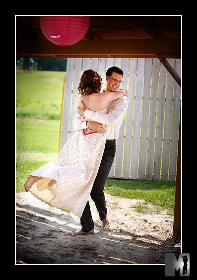 Groom lifts bride up while outside, white picket fence in background