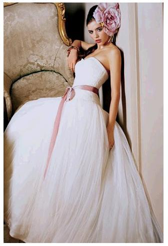 Vera Wang strapless wedding dress with dusty rose sash and oversized fascinator