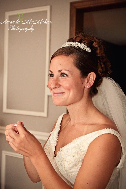 The bride's happy face shines in this classic picture of a bride with a simple updo and tiara.