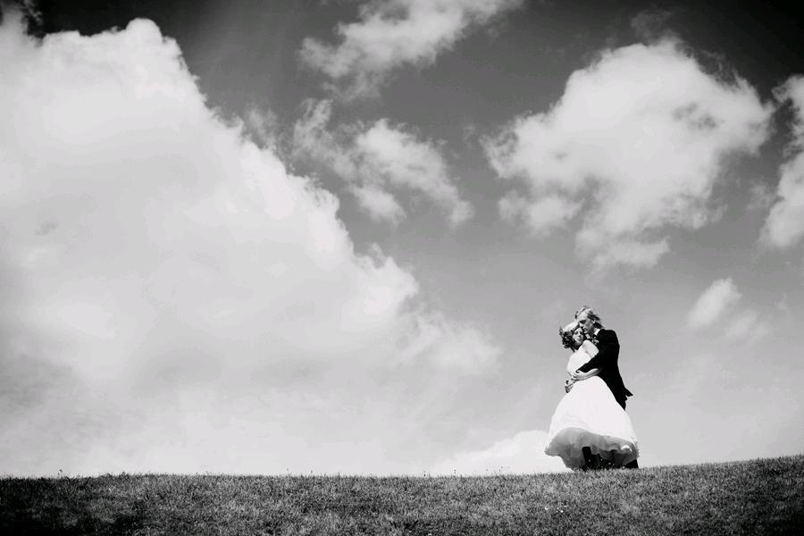 A-castle-wedding-european-romantic-black-and-white-wedding-photo-groom-holds-bride-outside-atop-hill-clouds-sky-in-background.full
