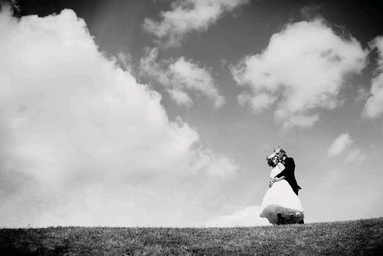 Bride and groom atop a hill, hold each other with a beautiful cloudy sky in the background