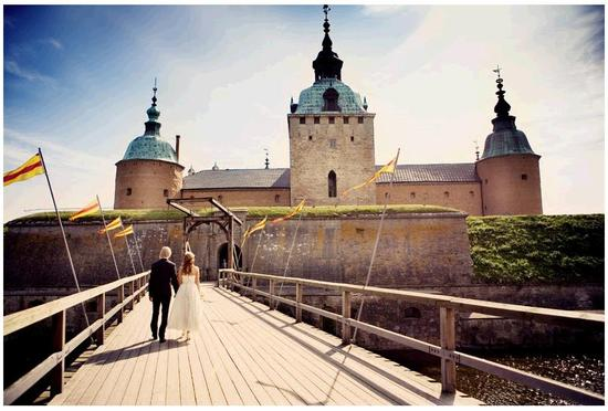 Bride and groom walk together hand in hand towards beautiful castle in Sweden