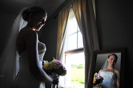 The bride views her strapless white wedding dress in the mirror while holding her pink and yellow bo