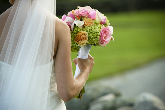 The bride's pink and yellow rose bouquet is wrapped in white fabric and provides an excellent compli