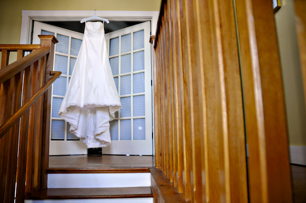 The strapless wedding dress is beautifully displayed against the long windows of the winery.
