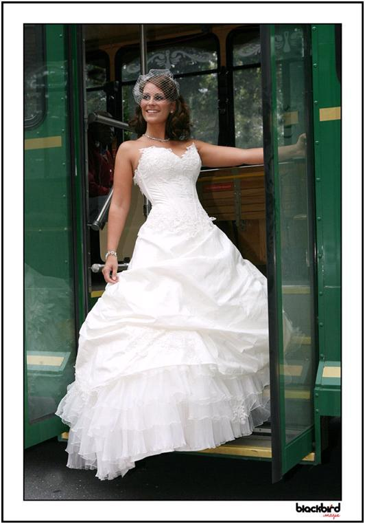Beautiful bride in white strapless wedding dress (sweetheart neckline) poses on trolley