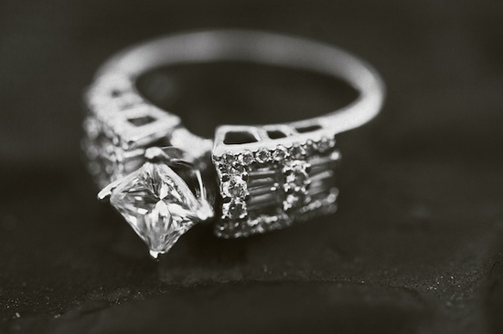 A stunning diamond engagement ring with a square center stone surrounded by other smaller diamonds.