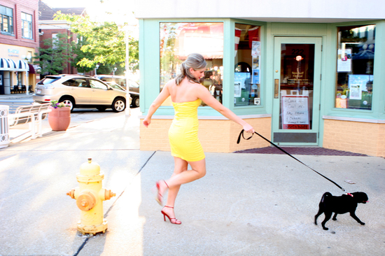 The blonde bride's sky-high red heels and bright yellow dress make walking her adorable black pug di