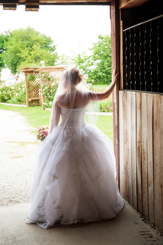 Karlee poses in entrance to Wedding Barn at the Civil War Ranch in Carthage, MO. Photo by Erin Mitchell Photography