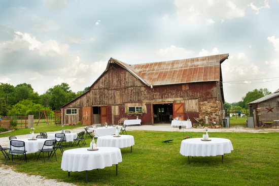 Tables and their centerpieces are set up in the Barn Courtyard at the Civil War Ranch in Carthage, MO. In the background is the Wedding Barn. Photo by Erin Mitchell Photography