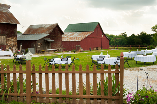 Tables and their centerpieces are set up in the Barn Courtyard at the Civil War Ranch in Carthage, MO.In the background is the Corn Crib and the West Barn. Photo by Erin Mitchell Photography