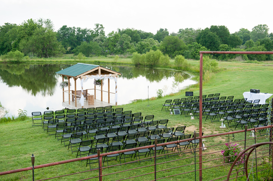 The dock and the north bank of the ranch pond is set up for the Talent wedding ceremony at the Civil War Ranch in Carthage, MO. Photo by Erin Mitchell Photography