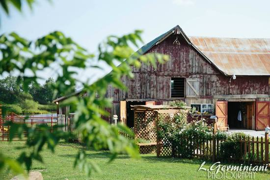 View looking south from outdoor arena parking lot at the Courtyard Rose Arbor and the Wedding Barn. Photo by L. Germiniani Photography