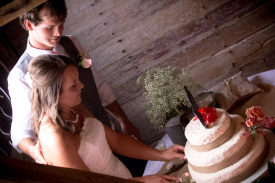 Bride and groom pose behind their wedding cake in the northwest nook of the first-floor banquet room in the Wedding Barn at the Civil War Ranch in Carthage, MO. Photography by Rebecca Olson