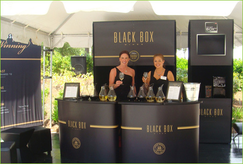 These women in stylish black dresses serve wine in a box by Black Box.