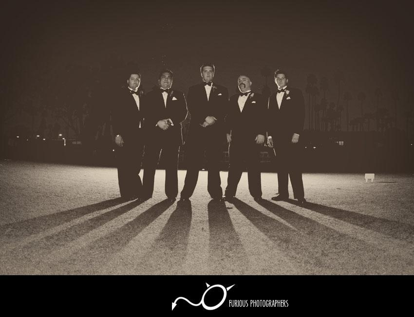 Shadow-of-groom-and-groomsmen-in-tuxes-stand-outside-black-white-in-parking-lot-look-tough.full