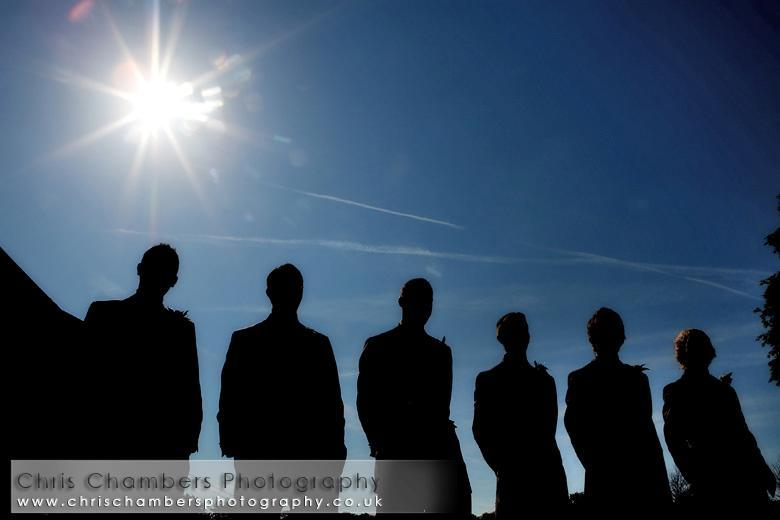 Shadow-of-groom-and-groomsmen-in-tuxes-stand-outside-blue-sky-bright-sun-shining.full