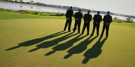 Groom and groomsmen stand in line on golf course donning tuxedos, shadows behind