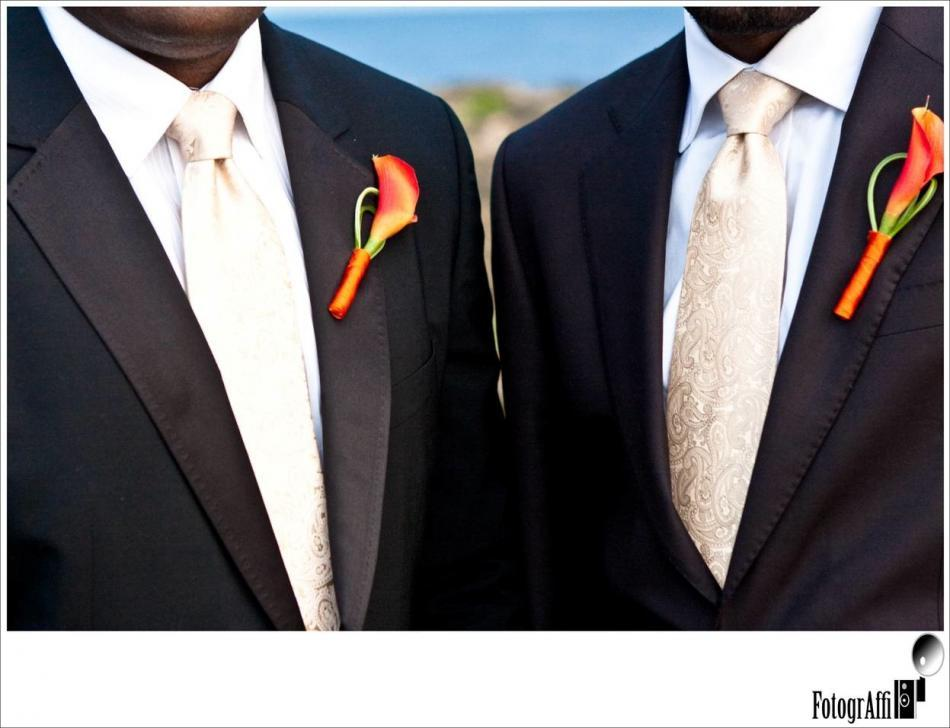 The orange boutonniere is a perfect complement to the dark suits and light colored ties.