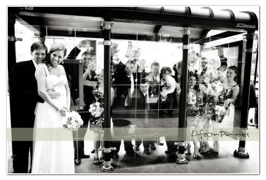 Bride, groom and wedding party have fun posing at bus stop in this black and white wedding photo