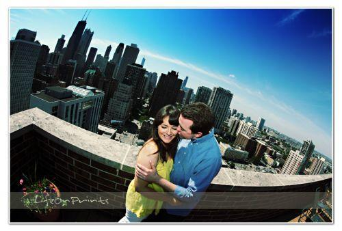Groom kisses bride while standing on balcony overlooking Chicago skyline