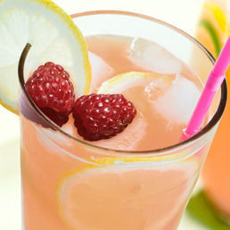 photo of Pink lemonade in a tall glass, garnished with lemon and raspberries.
