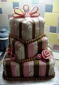 photo of Whimsical wedding cake with pink and brown stripes, delicate white and green flowers and a pink ribb