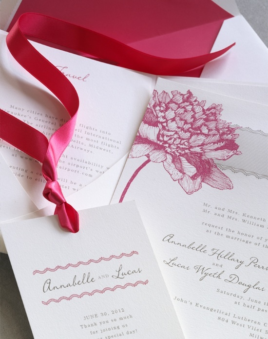 A pink peony graces this white wedding invitation with matching pink ribbon, designed by Vera Wang.