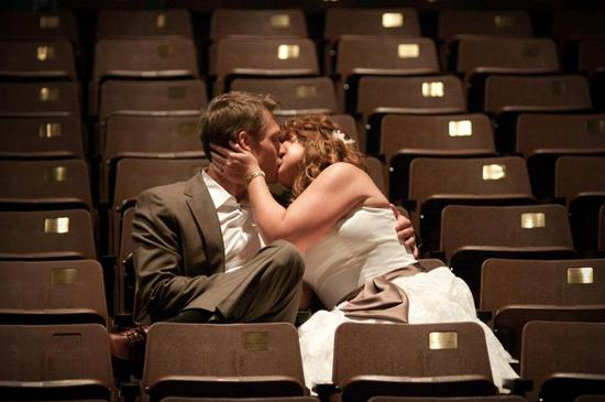 Bride in strapless dress with brown sash kisses groom in brown suit in stadium seats.