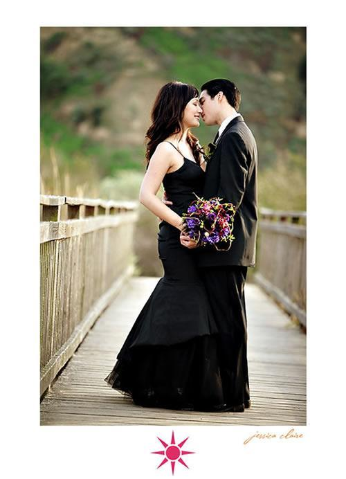 Bride in black wedding dress kisses groom, holds vibrant purple and fuschia bouquet